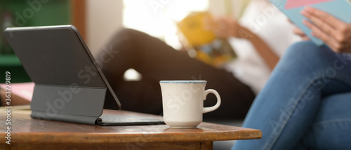 Obraz Digital tablet with keyboard and coffee cup on wooden coffee table in living room - fototapety do salonu