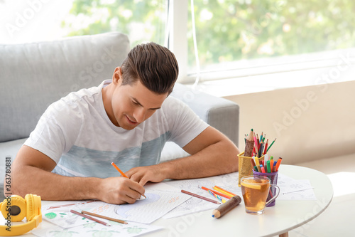 Fotografie, Obraz Young man coloring pictures at home