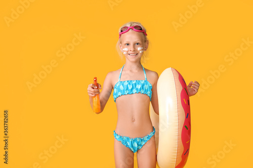 Fototapeta Little girl with sun protection cream and inflatable ring on color background obraz