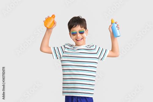 Fototapeta Little boy with sun protection cream on grey background obraz