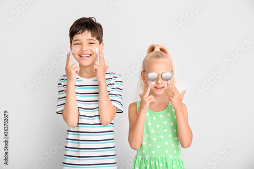 Fototapeta Little children with sun protection cream on their faces against grey background obraz