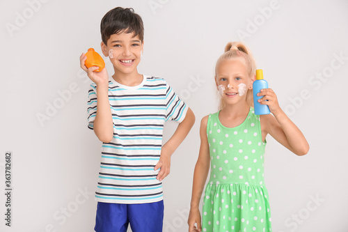 Fototapeta Little children with sun protection cream on grey background obraz
