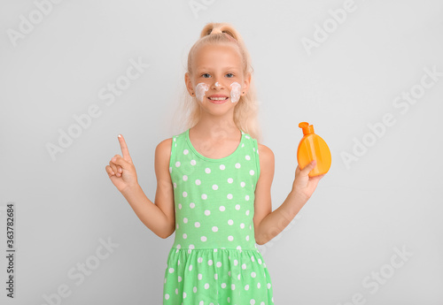 Fototapeta Little girl with sun protection cream on grey background obraz