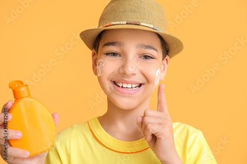 Fototapeta Little boy with sun protection cream on color background obraz