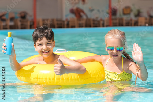 Fototapeta Little children with sun protection cream and inflatable ring in swimming pool obraz