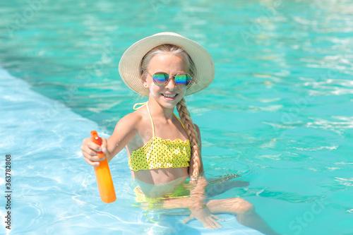 Fototapeta Little girl with sun protection cream in swimming pool obraz
