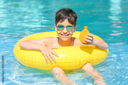 Fototapeta Little boy with sun protection cream and inflatable ring in swimming pool obraz