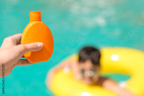 Fototapeta Mother with sun protection cream for her son in swimming pool obraz