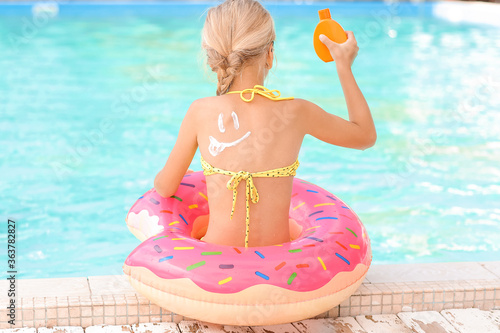 Fototapeta Little girl with sun protection cream and inflatable ring near swimming pool obraz