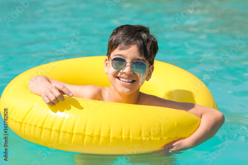 Fototapeta Little boy with sun protection cream on his face and inflatable ring in swimming pool obraz