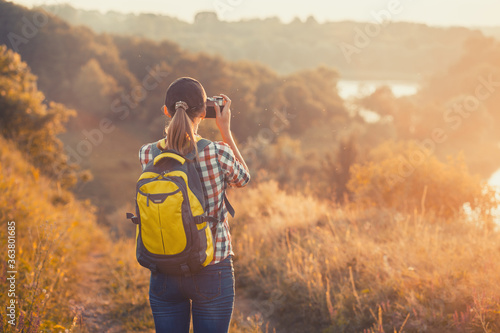 Fototapeta tourist girl with a backpack and a camera walks through a picturesque meadow and photographs the picturesque landscape. Tourism, outdoor activities obraz