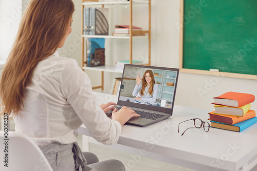 A teacher teaches a student online. Student girl is listening to teacher lecture having video call laptop at home.