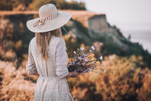 Beautiful Young Woman In A Hat On A High Sea Cliff With A Bouquet Of Flowers In A Retro Hat.