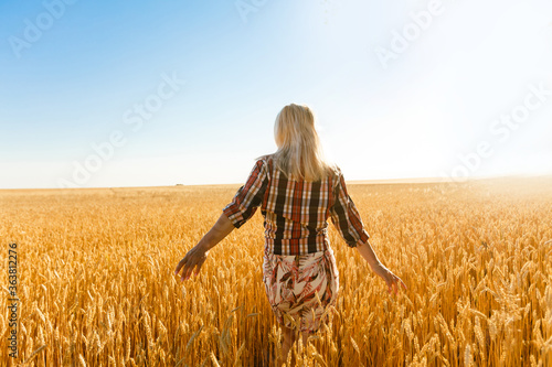 Photo Woman in a wheat field on the background of the setting sun