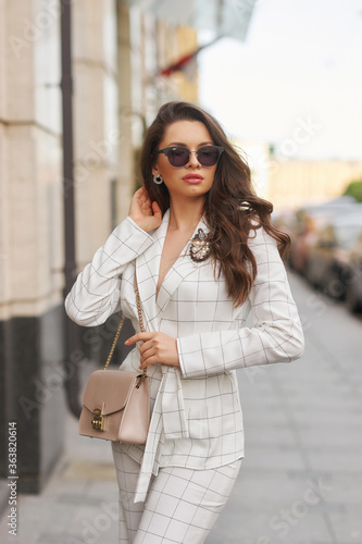 Obraz Young beautiful elegant woman in white casual costume walking at street on a summer day. Pretty lady wearing sunglasses and holding handbag. Businesswoman standing and posing in the city - fototapety do salonu