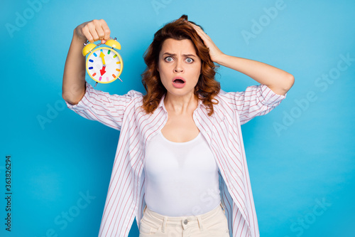 Fototapeta Portrait of her she nice attractive lovely puzzled worried wavy-haired girl holding in hand wake-up clock late first lecture isolated on bright vivid shine vibrant blue color background obraz