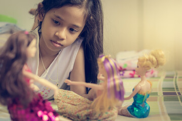 Little Girl Is Playing Dolls On Bed In Holiday.