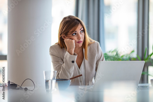 Shot of a young businesswoman looking bored while working at her desk in a modern office Wallpaper Mural