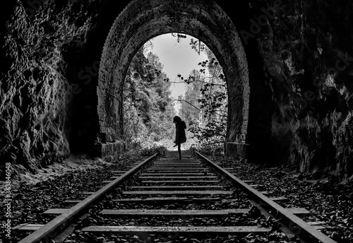 Fotografie, Obraz Rear View Of Silhouette Woman Standing On Railroad Track