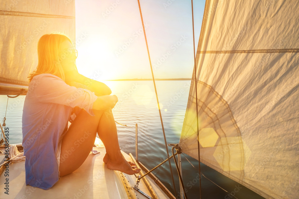 Fototapeta Young happy woman enjoying sunset from deck of sailing boat moving in sea at evening time. Travel, Summer, Holidays, Journey, Trip, Lifestyle, Yachting concept.