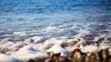 Fototapeta Kuchnia - Waves washing over gravel beach, macro shot.