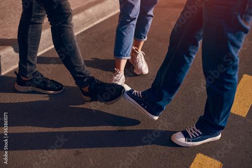 Fotografering Crop friends doing feet bump greeting