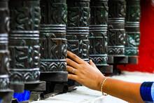 Cropped Image Of Hand Touching Prayer Wheel At Swayambhunath Temple