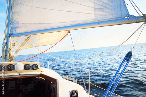 Fototapety, obrazy: White sailboat in an open sea on a clear sunny day, close-up view from the deck to the bow, mast and sails. Single handed sailing a 34 ft yacht. England, UK. Sport, racing, recreation