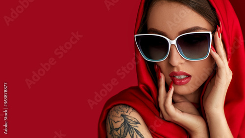 Fototapeta Portrait of beautiful brunette sexy woman with luxurious make-up in white sunglasses and red headscarf on red background. copy space for text obraz