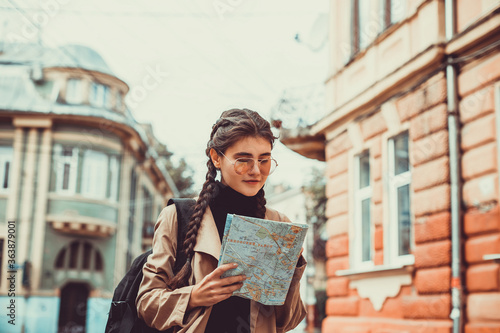 Young european tourist happy and excited walking in foreign city, using a map Fototapeta