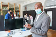 Businessman wearing face mask while disinfecting hands