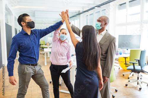 Business team with face mask giving the high five Poster Mural XXL