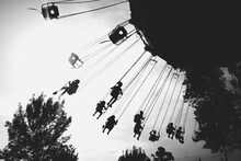 Low Angle View Of Silhouette People Enjoying Chain Swing Ride Against Sky