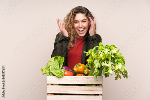 Farmer with freshly picked vegetables in a box isolated on beige background laughing