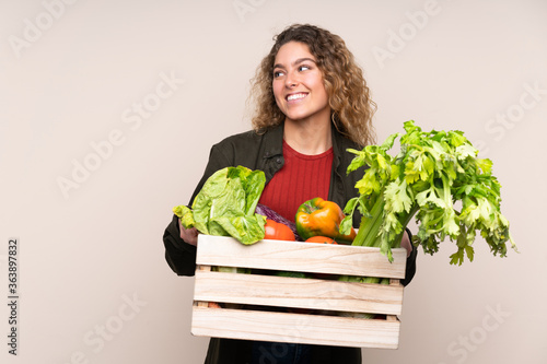 Farmer with freshly picked vegetables in a box isolated on beige background