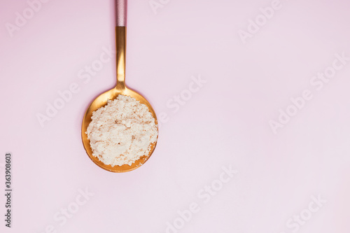 Collagen powder in a spoon on pink background