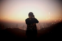 Rear View Of Silhouette Person Overlooking Cityscape