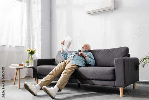 Fotografie, Obraz Tired senior man holding newspaper on couch under air conditioner at home