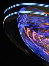 Light Trails At Amusement Park Ride Against Black Background