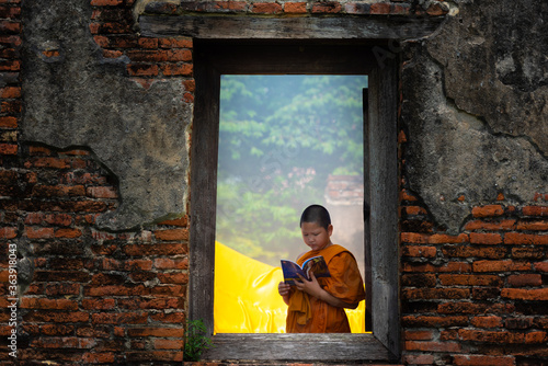 Boy Wearing Traditional Clothing Reading Book Seen Through Window Wallpaper Mural
