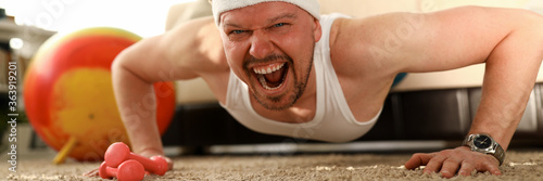 Obraz na plátně Man working out at home, training sportive male