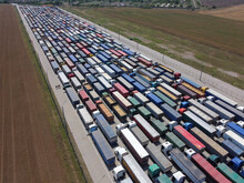Cargo Transportation And Logistics, Many Trucks In The Port Area Are Waiting For Their Turn To Unload. A Long Line Of Trucks With Grain.