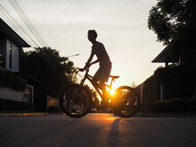 Low Angle View Of Boy Riding Bicycle On Street Against Sky During Sunset