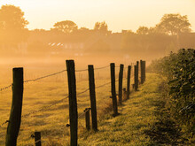 Wooden Posts On Field Against Sky During Sunset