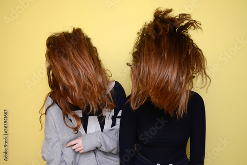 Two Girls On Yellow Background Tossing Hair Fototapet
