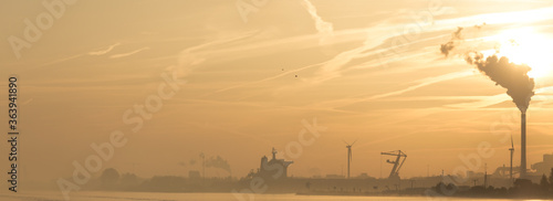 Foto Smoke Emitting From Factory In City By River Against Sky During Sunset