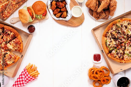 Fototapeta Frame with a variety of take out and fast foods. Pizza, hamburgers, fried chicken and sides. Top view on a white wood background with copy space. obraz