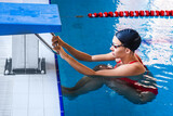 Fototapeta Tulipany - Young woman swimmer in a swimsuit getting ready to start a swimming in a swimming pool. Professional swimmer near the starting block .