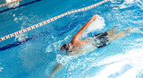 Fototapeta Tulipany - Man swimmer is swimming in the pool, backstroke technique swimming. Shot of swim in motion