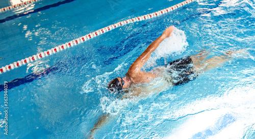Cuadros en Lienzo Man swimmer is swimming in the pool, backstroke technique swimming